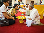 17 AUGUST 2014 - BANGKOK, THAILAND:      A Hindu priest anoints a woman during Krishna Janmashtami services at the Vishnu temple in Bangkok. Krishna Janmashtami is the annual celebration of the birth of the Hindu deity Krishna, the eighth avatar of the Hindu god Vishnu. It is celebrated by Hindus in Thailand. There are about 53,000 Hindus in Thailand, most originally from India, but many Hindu deities are highly revered by Thai Buddhists and Hindu holy days are observed by many Thai Buddhists.  PHOTO BY JACK KURTZ