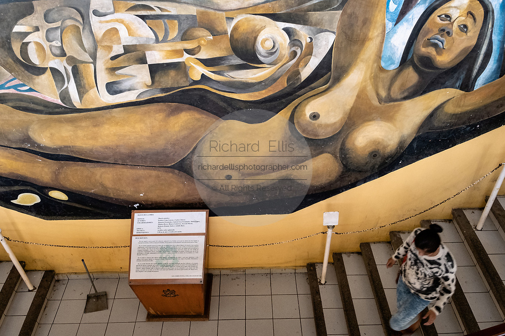 A woman walks past the Mural Collectivo celebrating the culture of the indigenous Olmec people at the Palacio Municipal San Andres Tuxtla in San Andres Tuxtlas, Veracruz, Mexico. The well known mural was created by famous muralist Teodoro Cano Garcia and Carlos Chavez.