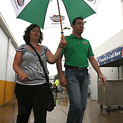 NASCAR Sprint Cup driver Kyle Busch walks in the rain to the drivers meeting prior to the 56th Annual NASCAR Coke Zero400 race at Daytona International Speedway on Saturday, July 5, 2014 in Daytona Beach, Florida.  (AP Photo/Alex Menendez)