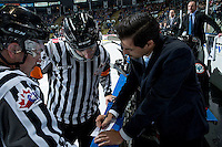 KELOWNA, CANADA - NOVEMBER 12: Kelowna Rockets' assistant coach, Travis Crickard stands at the boards speaking with ice officials, linesman Kevin Crowell and referee, Mike Langlin during a time out against the Prince Albert Raiders with  on November 12, 2016 at Prospera Place in Kelowna, British Columbia, Canada.  (Photo by Marissa Baecker/Shoot the Breeze)  *** Local Caption ***