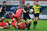 Dan Baker of the Ospreys is stopped by Ken Owens (on ground) and James Davies of the Scarlets. Guinness Pro12 rugby match, Ospreys v Scarlets at the Liberty Stadium in Swansea, South Wales on Saturday 26th March 2016.<br /> pic by  Andrew Orchard, Andrew Orchard sports photography.