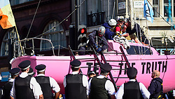 """© Licensed to London News Pictures. 19/04/2019. LONDON, UK. Police officers prepare to remove the last activist from the pink boat at Oxford Circus during """"London: International Rebellion"""", on day five of a protest organised by Extinction Rebellion.  Protesters are demanding that governments take action against climate change.  Police have issued a section 14 order requiring protesters to convene at Marble Arch only so that the protest can continue.  Photo credit: Stephen Chung/LNP"""