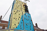 Adam, a child on the estate enjoying the climbing wall at the Pathways Project launch by Souther Housing Group, Stamford Hill Estate London. The pathways project is a voluntary information, support and guidance service aimed at young people aged 16-25 years in Hackney.