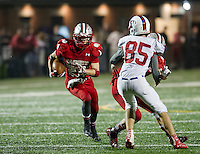 Laconia's Drew Muzzey carries the ball with a block on Trinity's Jacob Brown by Laconia's Bradley Weeks during Friday night football at Jim Fitzgerald Field.  (Karen Bobotas/for the Laconia Daily Sun)