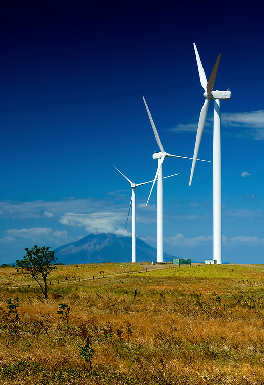 Wind turbines on the shores of Lake Nicaragua.  Concepcion Volcano can be seen rising in the background on the Island Of Ometepe.