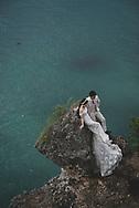 Balangan Beach, Bali, Indonesia - March 16, 2017: A couple pose for wedding photos on a bluff high above the ocean at Balangan Beach.