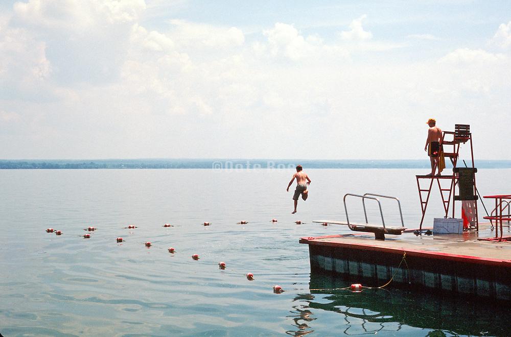 Boy jumping mid-air off of a diving board at a lake