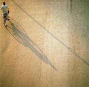Man riding bike casts a shadow across street, Lucknow, Uttar Pradesh, India