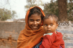 Young woman standing in street holding baby smiling,