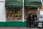 Two Jehovahs Witnesses stand with copies of the Watchtower magazine next to a shop window of assorted snacks on shelves in a corner shop convenience store on Gerrard Street, Chinatown, on 5th March 2018, in London, England.