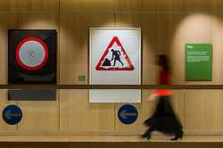 "© Licensed to London News Pictures. 20/10/2020. LONDON, UK.  London, UK.  20 October 2020. A staff member passes ""Woman at Work"", 2018, by Margaret Calvert.  Preview of Margaret Calvert: Woman at Work at the Design Museum in Kensington.  The exhibition explores the graphic designer's influence on the UK's visual identity and continuing impact through projects such as the new Rail Alphabet 2 typeface for Network Rail.  Photo credit: Stephen Chung/LNP"