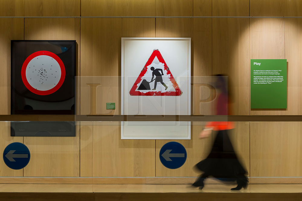 """© Licensed to London News Pictures. 20/10/2020. LONDON, UK.  London, UK.  20 October 2020. A staff member passes """"Woman at Work"""", 2018, by Margaret Calvert.  Preview of Margaret Calvert: Woman at Work at the Design Museum in Kensington.  The exhibition explores the graphic designer's influence on the UK's visual identity and continuing impact through projects such as the new Rail Alphabet 2 typeface for Network Rail.  Photo credit: Stephen Chung/LNP"""