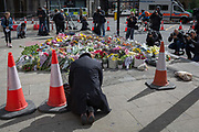 Three days after the terrorist attack in which 7 people died and many others suffered life-changing injuries on London Bridge and Borough Market, a gentelman bows to pray near a shrine of flower tributes which has grown near the crime scene site, on 6th June 2017, on London Bridge, in the south London borough of Southwark, England. City commuters now back at work walk respectfully and quietly past the floral memorial at the plinth marking the southern boundary of the City of London, the capitals financial district.