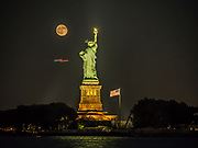 The moon shines at the Statue of Liberty National Monument in New York Harbor.