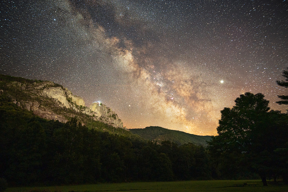 A group of climbers near the top of Seneca Rocks in West Virginia, as twilight ends and the Milky Way makes an appearance high above the mountains.