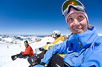 Young woman smiling at camera while snowboarding at Kirkwood resort near Lake Tahoe, CA.