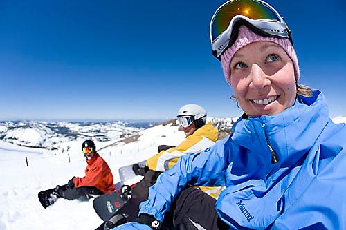Young woman smiling at camera while snowboarding at Kirkwood resort near Lake Tahoe, CA.