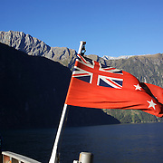 Tourists on a cruise ship flying the New Zealand flag on Milford Sound, South Island, New Zealand..Milford Sound (Piopiotahi in Ma¯ori) is a fjord in the south west of New Zealand's South Island, within Fiordland National Park and the Te Wahipounamu World Heritage site. It has been judged the world's top travel destination and is acclaimed as New Zealand's most famous tourist destination..Milford Sound runs 15 kilometres inland from the Tasman Sea at Dale Point - the mouth of the fiord - and is surrounded by sheer rock faces that rise 1,200 metres (3,900 ft) or more on either side. Among the peaks are The Elephant at 1,517 metres (4,977 ft), said to resemble an elephant's head and The Lion, 1,302 metres (4,272 ft), in the shape of a crouching lion. Lush rain forests cling precariously to these cliffs, while seals, penguins, and dolphins frequent the waters and whales can be seen sometimes..Milford Sound sports two permanent waterfalls all year round, Lady Bowen Falls and Stirling Falls. After heavy rain many hundreds of temporary waterfalls can be seen running down the steep sided rock faces. .The beauty of this landscape draws thousands of visitors each day, with between 550,000 and 1 million visitors in total per year. This makes the sound one of New Zealand's most-visited tourist spots, and also the most famous New Zealand tourist destination.  Milford Sound, New Zealand. 29th April 2011. Photo Tim Clayton