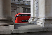 Red London Routemaster bus beneath Cornhill pillar and the wall of the Bank of England.