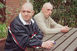 Two male residents sitting on bench in front garden of homeless hostel for people with learning difficulties,