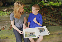 Carer reading outside with teenage boy with autism,