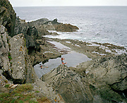 Two girls jump in and swim in Chapel Pool, Polperro, Cornwall, UK. Until the 1950s and the rise of the heated indoor swimming pool, children learnt to swim outdoors. For those close to the sea, many man-made tidal swimming pools were constructed around Britain's coastline. Heated by the sun, these tidal pools were often built to keep bathers safe from high and rough seas, which explains why so many of them are clustered in Scotland and around the surfing beaches of Cornwall. Whether they are simple swimming holes made by shoring up natural rock pools or grand lido-like pools complete with lifeguards and tea huts, they are all refreshed by good high tides.