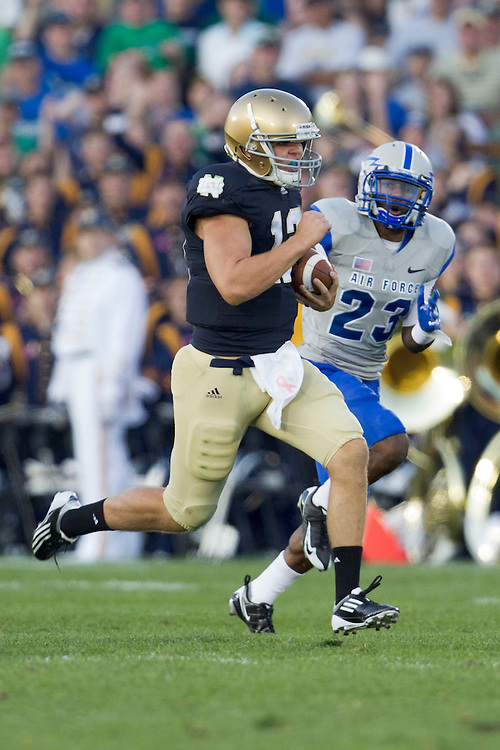 Notre Dame quarterback Andrew Hendrix (#12) runs the ball from scrimmage as Air Force defensive back Steffon Batts (#23) defends in action during NCAA football game between Notre Dame and Air Force.  The Notre Dame Fighting Irish defeated the Air Force Falcons 59-33 in game at Notre Dame Stadium in South Bend, Indiana.