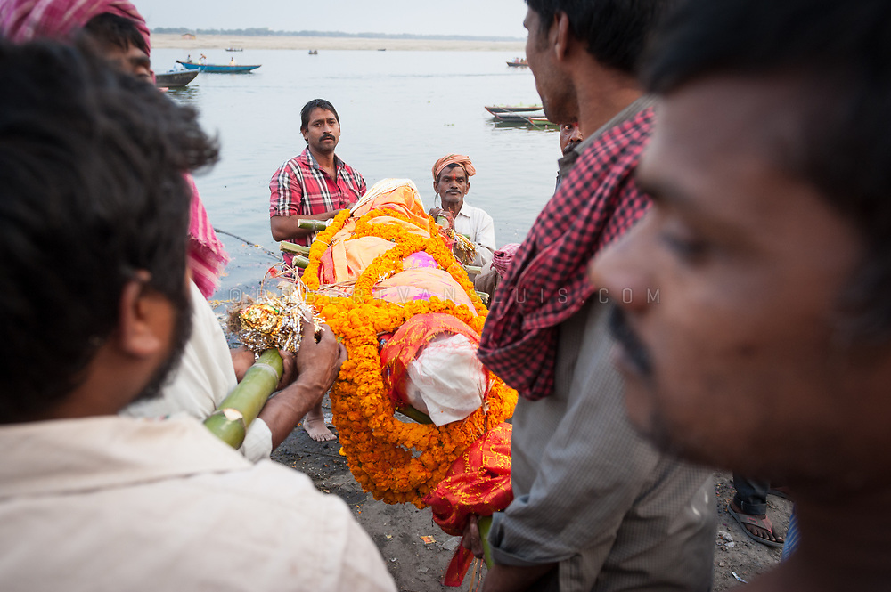 Family members carry the decorated body to the Ganges River at Manikarnika cremation ground, Varanasi, India. Photo ©robertvansluis.com