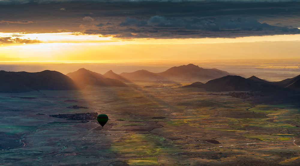 Hot-air balloon at sunrise against atmospheric cloudy sky, in Marrakech, Morocco.