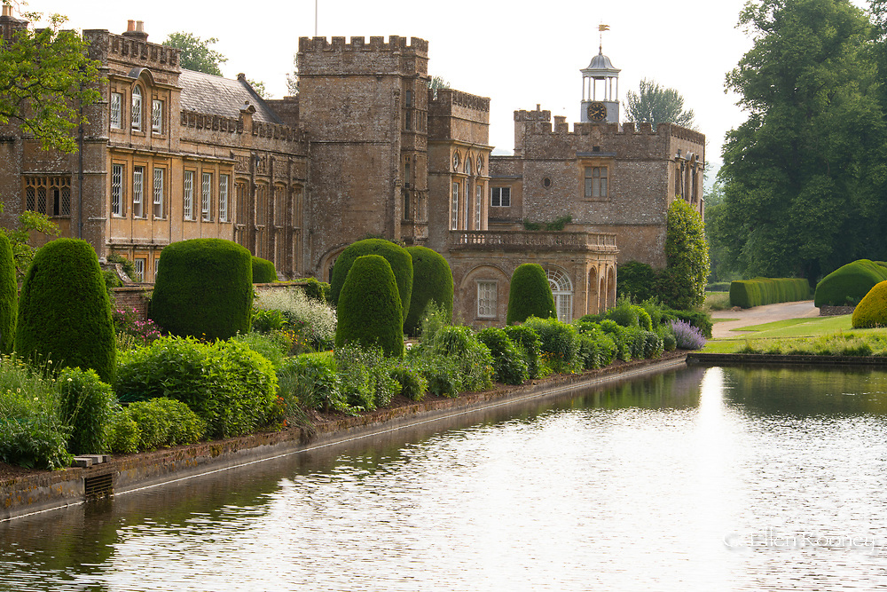 Herbaceous borders and cliiped Yew topiary around the long pond at Forde Abbey, Chard, Dorset, UK