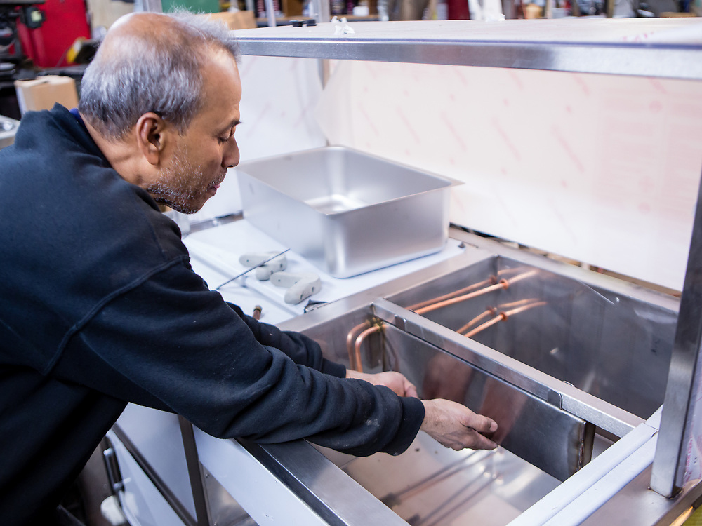 Jasim Uddin holds a water heater in place in a food cart being built for Nathan's Famous hot dogs. Cold water is heated by the burners under the bain-marie, and flows to the sink.