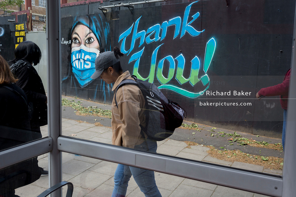 On the day that the UK death rate during the Coronavirus pandemic surpasses 40,000, including almost 10,000 care home residents, the highest rate in Europe, Londoners walk past a mural created by the anonymous street artist known as 'Artful Dodger' (after Charles Dickens's pickpocket character in Oliver Twist), of a Muslim NHS (National Heath Service) nurse wearing a surgical face mask, at Elephant & Castle in south London, on 121th May 2020, in London, England.
