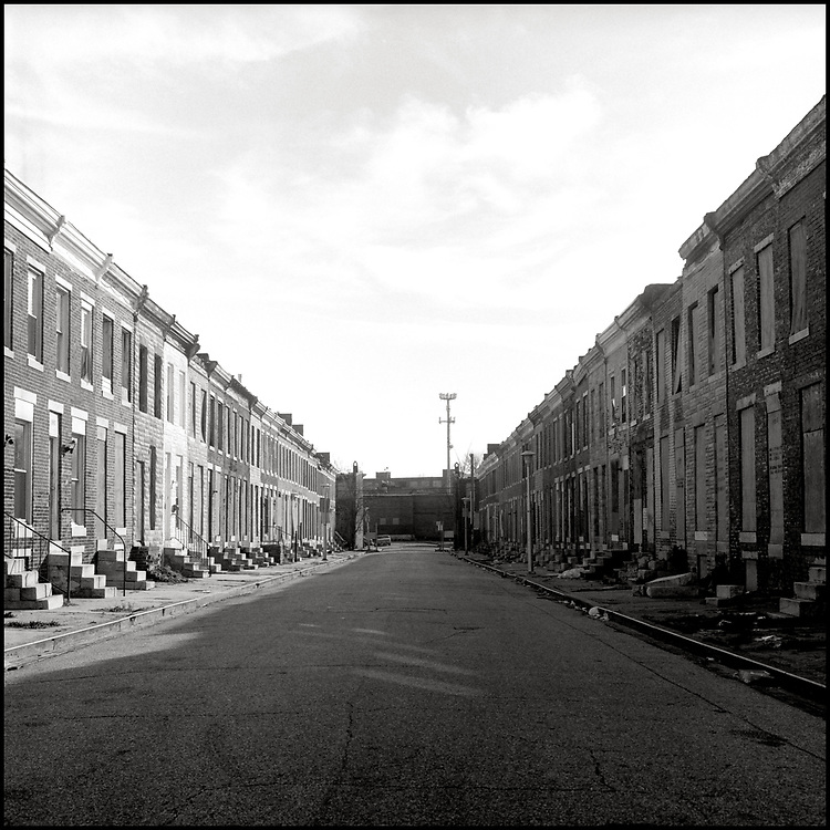 """Many neighborhoods in Baltimore contain street after street of boarded up homes, closed storefronts, cracked sidewalks, and trash-filled alleyways. This blight was caused by similar factors as in other cities, including neighborhood """"blockbusting"""", redlining, urban renewal, a tax & regulatory governing model, the loss of manufacturing jobs and increased poverty."""