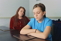 Teenage girl sitting at table looking moody with her mother looking angry in the background,
