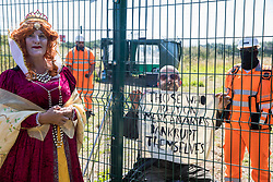 Environmental activists in period costume from groups opposed to the HS2 high-speed rail link, one of which on the other side of the security fence, restage a historical 1602 visit by Queen Elizabeth I to Dews Farm on 31st July 2020 in Harefield, United Kingdom. The activists tried to retrace the steps of Queen Elizabeth I from St Mary's church to Dews Farm in order to pay their respects to Anne and Ron Ryall, 73 and 72, on the day of their eviction from Dews Farm by HS2 after having spent nine years and their life savings renovating their £1m dream home, but found their path blocked by HS2 fences and security guards.