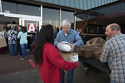 November 18, 2018 - Canton, GA - Volunteers from Action Church distribute 400 turkeys and boxes of grocery items to area families  with limited resources. The church is located in a modest storefront in a low-income part of town, and focuses community service as a priority.  The church has no official members.  Its volunteer, unpaid pastor Gary Lamb resists conventional ideas of what church should be. He calls this event 'Give Canton The Bird.' Pictured: Volunteers distribute frozen turkeys and boxes of food to low-income families (Credit Image: © Robin Rayne/ZUMA Wire)