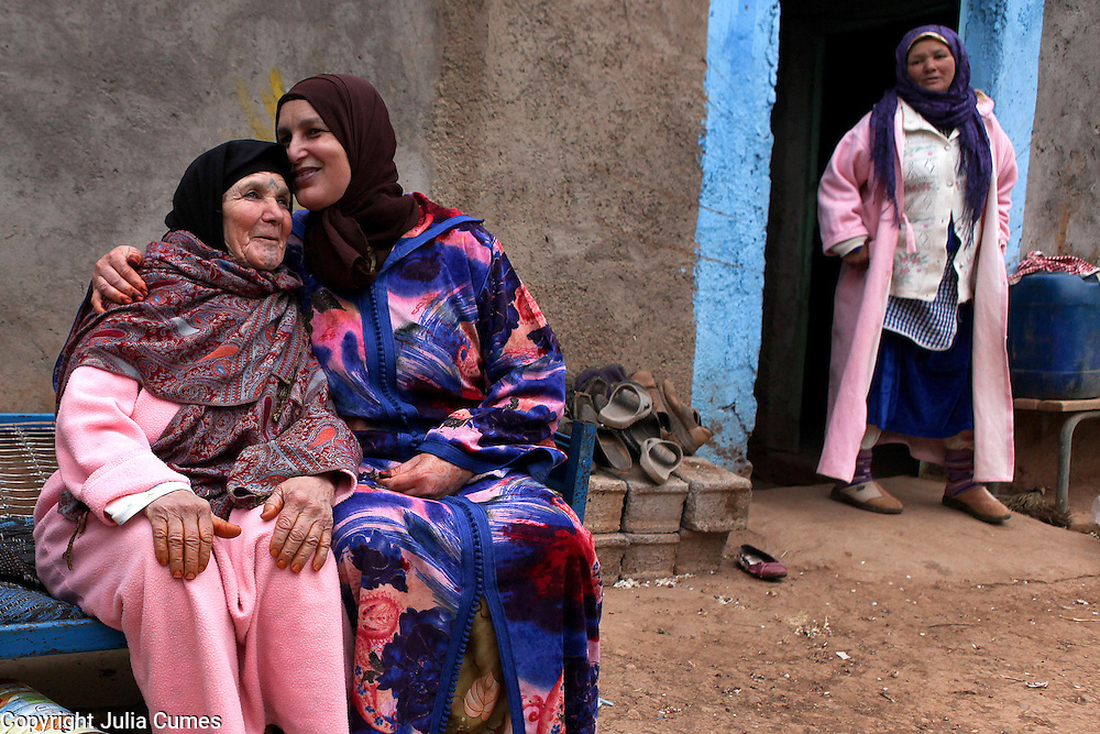 """Khina Boujnoui and her daughter, Fatima, share a moment of affection outside the family's home in Tamda, Morocco. The women are part of a traditional Berber family that has been weaving for generations. """"Weaving is the way we express ourselves,"""" says Fatima whose own daughter wants to attend university and has been less enthusiastic about the family's tradition."""