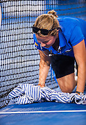 An Australian Open tournament official mops rainwater from under the center court net at Rod Laver Arena in Melbourne. A shower deluged the venue for a few minutes before the arena roof could be slowly closed.