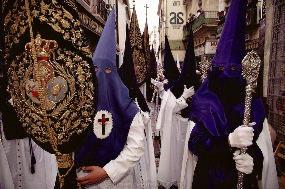 Hooded penitents in a procession during Holy week in Seville, Spain. Street processions are organized in most Spanish towns each evening, from Palm Sunday to Easter Sunday. People carry statues of saints on floats or wooden platforms, and an atmosphere of mourning can seem quite oppressive to onlookers