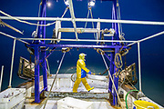 Luke dressed in his yellow oil skins prepares the lines ready to start pulling in the last catch of the night.  Luke is a Folkestone based fisherman out trawling for a 12 hour night shift on a fishing trip in his boat Valentine FE20, Hythe Bay, the English Channel, United Kingdom.