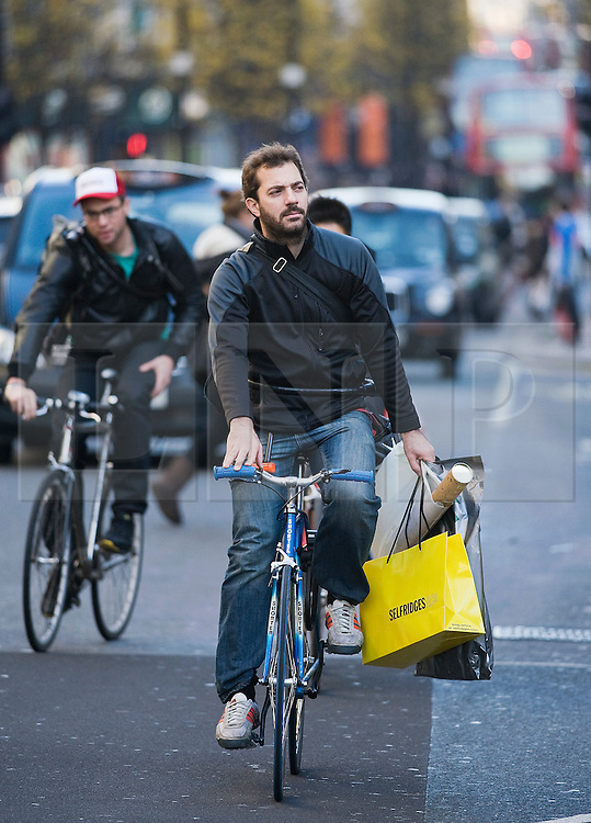 © Licensed to London News Pictures. 22/12/2011. London, UK. A Shopper carrying his shopping bags home on his bike on Oxford Street, London on December 22, 2011 . Tomorrow is expected to be the busiest shopping day of the year as the mad dash for last minute purchases begins.  Photo credit: Ben Cawthra/LNP