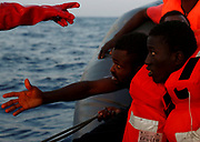 Migrants on board a rubber dinghy await rescue by the Malta-based NGO Migrant Offshore Aid Station (MOAS) in the central Mediterranean Sea, north of Sabratha, on the Libyan coast, April 5, 2017. REUTERS/Darrin Zammit Lupi