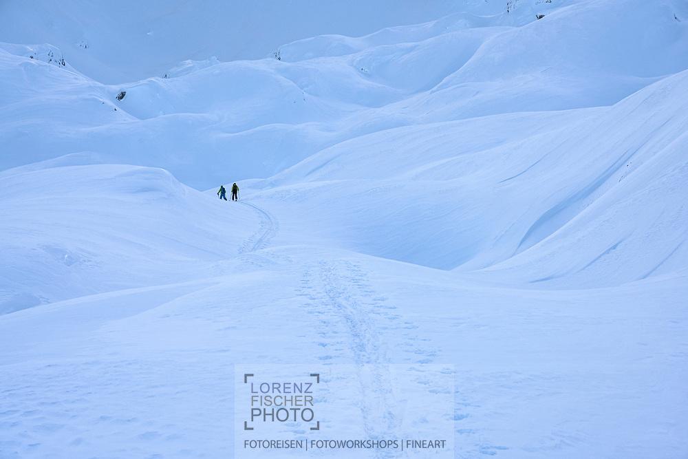 Two ski tourers on the way up to Blüemberg, Riemenstaldnertal, Schwyz, Switzerland