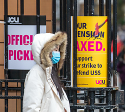© Licensed to London News Pictures. 04/03/2020. London, UK. A students at UCL walks past the UCU picket line wearing a mask as top medical chief warns spread of Coronavirus is highly likely and wearing masks will not stop infections . Photo credit: Alex Lentati/LNP