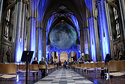 © Licensed to London News Pictures. 15/08/2021. Bristol, UK. Luke Jeram's Moon installation in Bristol Cathedral. Measuring seven metres in diameter, the Museum of the Moon features detailed NASA imagery of the lunar surface. At an approximate scale of 1:500,000 each centimetre of the internally lit spherical sculpture represents 5 km of the moon's surface. The Museum of the Moon  is open until 30 August 2021. Photo credit: Dinendra Haria/LNP