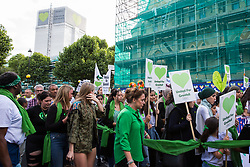 London, UK. 14th June, 2018. Members of the Grenfell community and supporters pass in front of the Grenfell Tower on the Grenfell Silent March through West Kensington on the first anniversary of the Grenfell Tower fire. 72 people died in the Grenfell Tower fire and over 70 were injured.