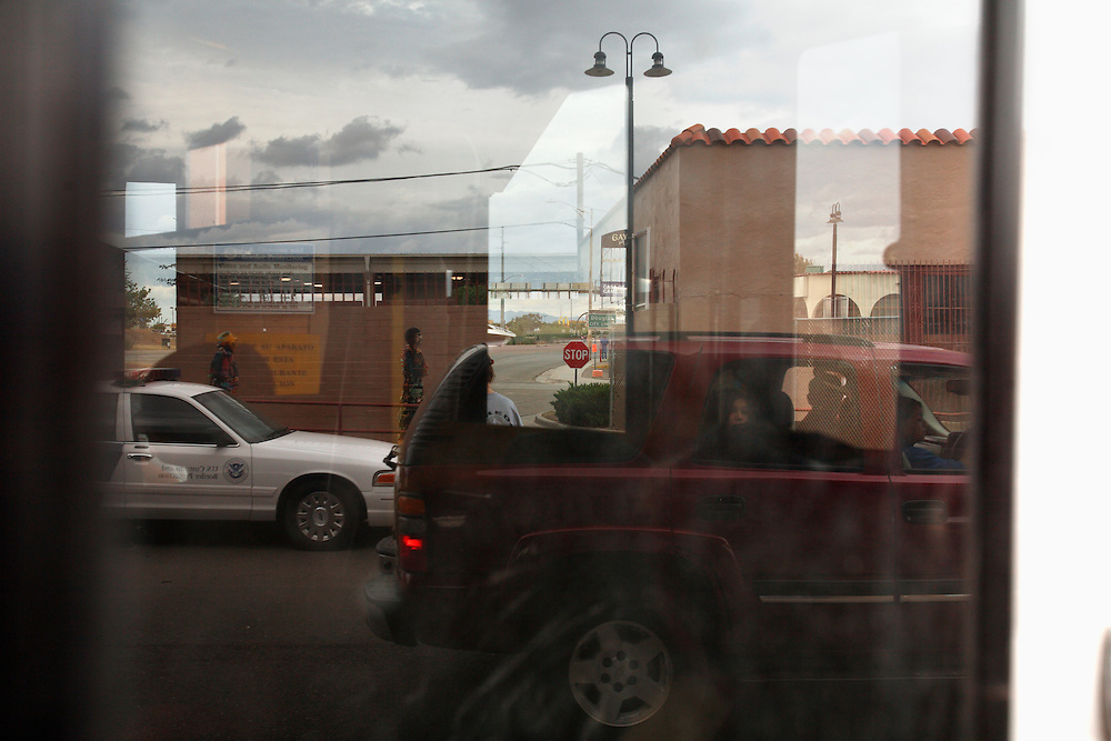 Reflections are seen in car windows at the United States Border Station in Douglas, Arizona, which borders Agua Perieta, Mexico. Hundreds of undocumented immigrants pass across the desert here, and dozens die every year from dehydration and exposure.