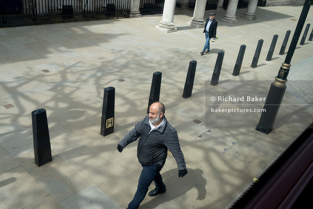 Two striding male strangers walk while separated by security bollards on Whitehall in Westminster, the centre of British government, on 27th April 2021, in London, England.