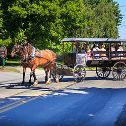 Intercourse, PA - June 18, 2016: Tourists leave on a tour of rural farmland in a horse-drawn wagon.