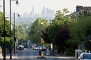 With the London skyline in the far distance, a dog walker crosses the steep gradient of Gypsy Hill in Crystal Palace, on 16th June 2021, in London, England.